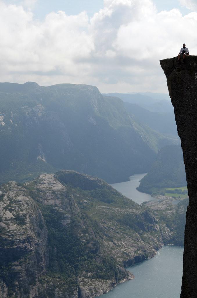 Manolito sentado en el borde del Púlpito con todo el fiordo a la derecha y un fallal gigante de piedra
