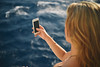 Woman-Using-Smartphone-With-Beautiful-Blue-Ocean