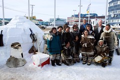 U.S. Secretary of State John Kerry, flanked by Canadian Member of Parliament Leona Aglukkaq of Canada and Canadian Foreign Minister Robert Nicholson, poses with aboriginal northerners at a replica Inuit village in Aglukkaq's hometown of Inaquit, Canada, just below the Arctic Circle, after the United States assumed a two-year chairmanship of the body during a meeting of its eight member nations and seven Permanent Representatives on April 24, 2015. [State Department photo/ Public Domain]