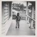 Small photo of Young African American boy standing on a porch
