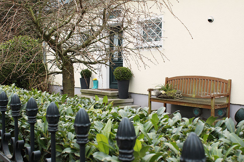 Hauseingang mit Buchsbäumen, Bank und Gummistiefeln