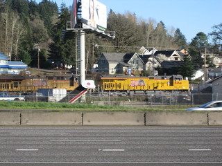 A UP freight sails by on the other side of the freeway