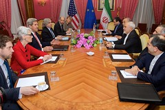 U.S. Secretary of State John Kerry - flanked by Under Secretary of State for Political Affairs Wendy Sherman, U.S. Energy Secretary Dr. Ernest Moniz, National Security Council Senior Director for Iran, Iraq, Syria and the Gulf States Robert Malley, and European Union Deputy Secretary General Helga Schmid - sits across from Iranian Foreign Minister Javad Zarif, Dr. Ali Akbar Salehi, the Vice President of Iran for Atomic Energy and President of the Atomic Energy Organization of Iran, and other advisers on March 27, 2015, in Lausanne, Switzerland, before resuming negotiations about the future of Iran's nuclear program. [State Department Photo / Public Domain]
