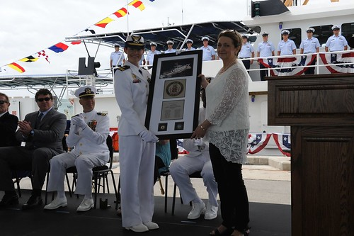 Audie N. Dodson, sponsor of the U.S. Coast Guard Cutter Isaac Mayo, receives a plaque with the cutter's coin from Lt. Ginny R. Nadolny, commanding officer of the Isaac Mayo, during the cutter's commissioning ceremony at Coast Guard Sector Key West, Fla., March 28, 2015.  Dodson is the great-great-great granddaughter of the cutter's namesake. U.S. Coast Guard photo by Lt. j.g. Pete Bermont.