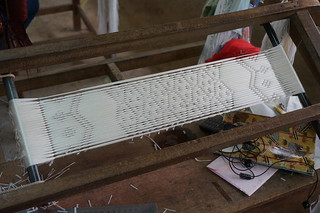 They create a pattern with plastic strips before dyeing