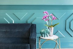 pink potted orchid with a ceramic blue elephant blue sofa