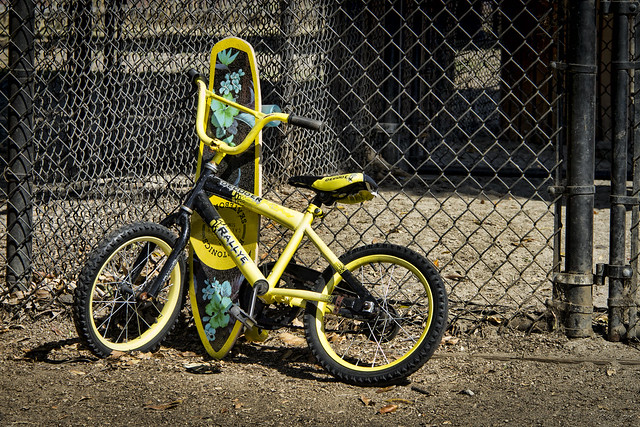 Yellow bike and skateboard