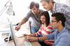 Teacher with students working on desktop