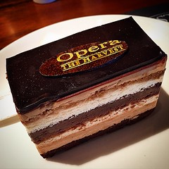 """Opera Cake, It is made with layers of almond sponge cake (known as Joconde in French) soaked in coffee syrup, layered with ganache and coffee buttercream, and covered in a chocolate glaze. According to Larousse Gastronomique, """"Opéra gateau is an elaborate"""