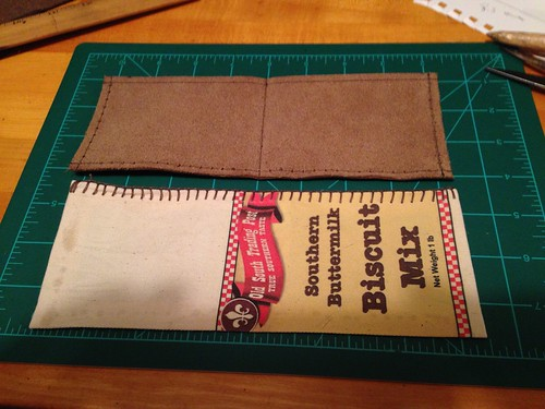 Since I had some leather, waxed thread of various sizes and a small canvas bag from a biscuit mix laying around, I made a wallet.