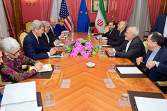 U.S. Secretary of State John Kerry - flanked by Under Secretary of State for Political Affairs Wendy Sherman, U.S. Energy Secretary Dr. Ernest Moniz, National Security Council Senior Director for Iran, Iraq, Syria and the Gulf States Robert Malley, and European Union Deputy Secretary General Helga Schmid - sits across from Iranian Foreign Minister Javad Zarif, Dr. Ali Akbar Salehi, the Vice President of Iran for Atomic Energy and President of the Atomic Energy Organization of Iran, and other advisers on March 26, 2015, in Lausanne, Switzerland, before resuming negotiations about the future of Iran's nuclear program. [State Department photo/ Public Domain]