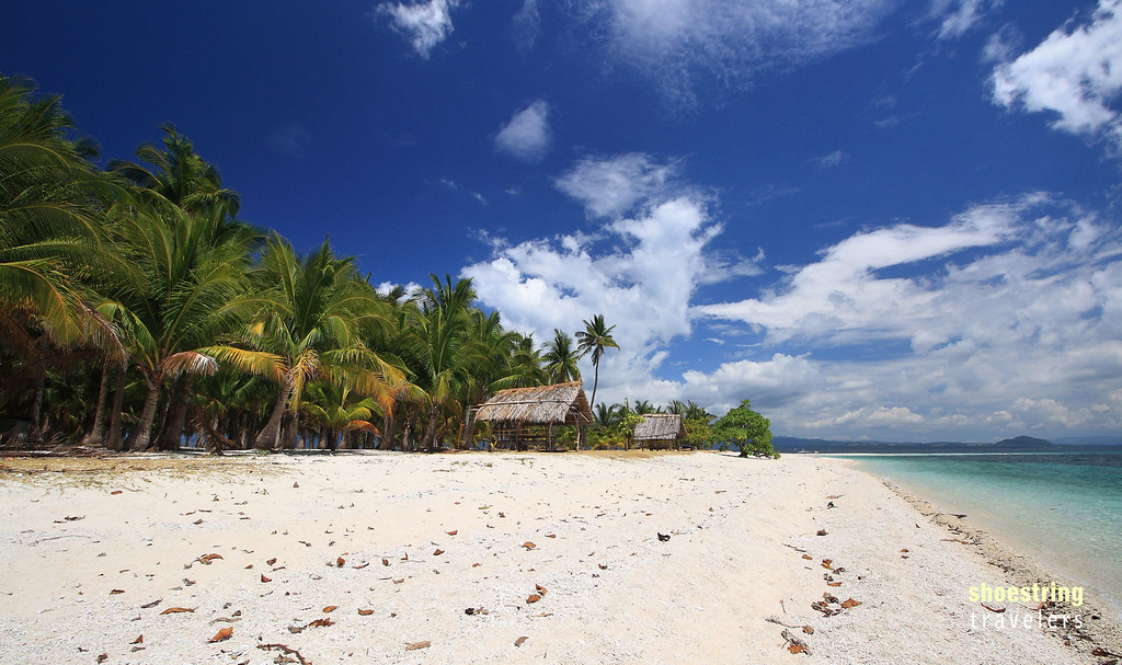 huts, palms and white sand beach at Digyo Island, Cuatro Islas