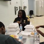 February 18, 2016 - 12:05 - The number of juvenile inmates in the Marion County Jail usually hovers around 40, but the command staff of the Jail understands that this population of inmates are still developing mentally and still need the care and attention of adults. Jail Commander James Martin and Major Tanesha Crear ordered a special lunch of cheeseburgers and chips in early 2016, and sat down with the juveniles to listen to what they have to say, and to also inform them of some upcoming programs based on good behavior. This photo of Major Tanesha Crear laughing with these young inmates really captures the heart of our Sheriff's Deputies in the Jail Division.