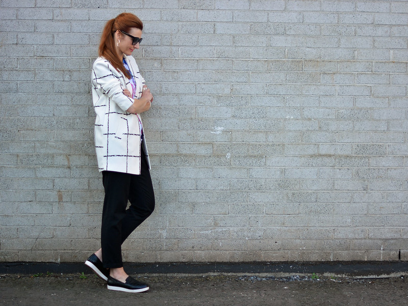 Mixed patterns: Windowpane check coat, graphic t-shirt, black trousers and slip on sneakers