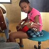 Evania playing guitar at the music class