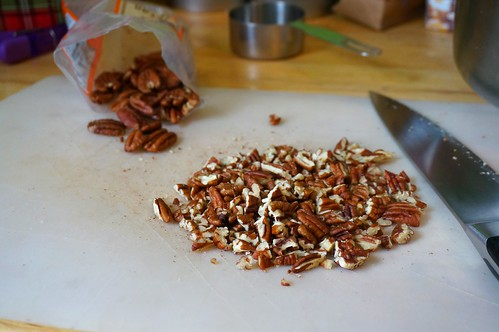 Chopped pecans piled on a cutting board, with pecan halves spilling out of a bag in the background