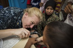 U.S. Navy Lt. Cmdr. Christina Olson examines a young boy's tonsils during the health festival held at Gumum Village in Chini, Malaysia, as part of Pacific Partnership. (RAAF/CPL David Cotton)