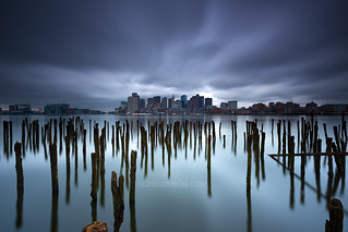 Downtown Boston Skyline over Sea of Decayed Pilings under Stormy Sky, East Boston Massachusetts