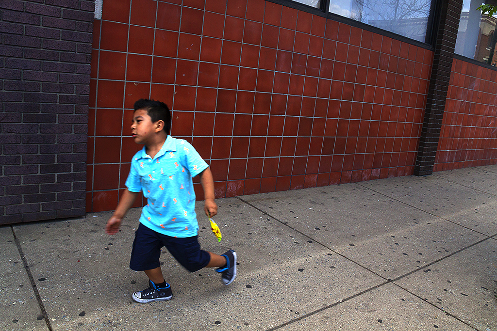 Boy running outside clinic on 5-19-16--Italian Market