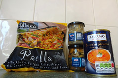 "Groceries lined up against a white tiled wall: a colourful plastic bag with a picture of rice and vegetables and the words ""Culinea / Paella / with Alaska Pollock Fillet Pieces, Mussels, Cooked Chicken Breast and Prawns""; glass jars of Nixe-brand cockles and mussels, and a can showing a bowl of red soup with a blob of cream in the middle and the words ""Italiamo / all italiana / Zuppa ai peperoni / Pepper Soup with Chilli""."