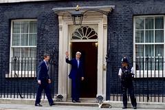 U.S. Secretary of State John Kerry, escorted by Special Adviser to the Prime Minister Nigel Casey, waves to reporters before entering No. 10 Downing Street in London, U.K., on June 27, 2016, to speak with Cameron following a meeting with the Secretary's counterpart, British Foreign Secretary Philip Hammond, in the aftermath of last week's 'Brexit' vote by the British people. [State Department Photo/ Public Domain]