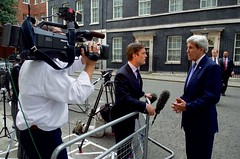 U.S. Secretary of State John Kerry speaks to NBC News Correspondent Keir Simmons while departing from No. 10 Downing Street in London, U.K., on June 27, 2016, after speaking privately with British Prime Minister David Cameron following another meeting with the Secretary's counterpart, British Foreign Secretary Philip Hammond, in the aftermath of last week's 'Brexit' vote by the British people. [State Department photo/ Public Domain]