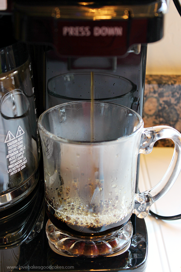 A coffee pot dispensing coffee in a cup.