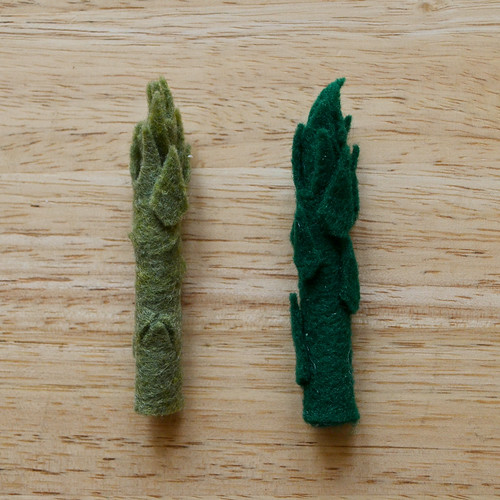 Step 5: Cut little triangles from scrap felt and hot glue to asparagus stalks, 3-4 triangles per stalk