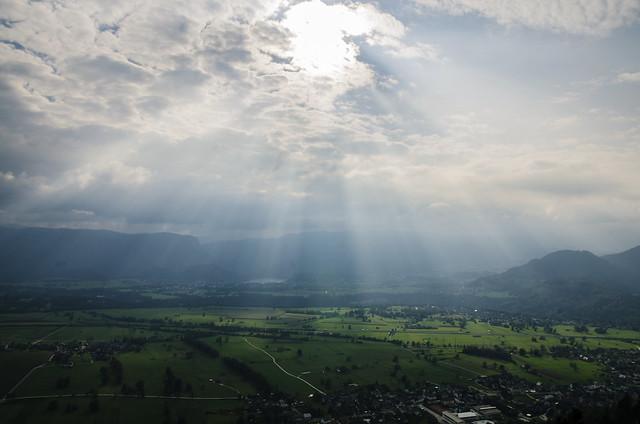 Sunlight Through Clouds Illuminating a Green Valley