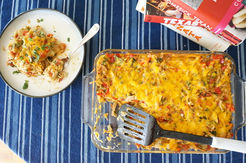 A serving of King Ranch chicken sits on a small plate, next to the full pan of the casserole with a spatula still sitting in it; a stack of Texas cookbooks is in the background