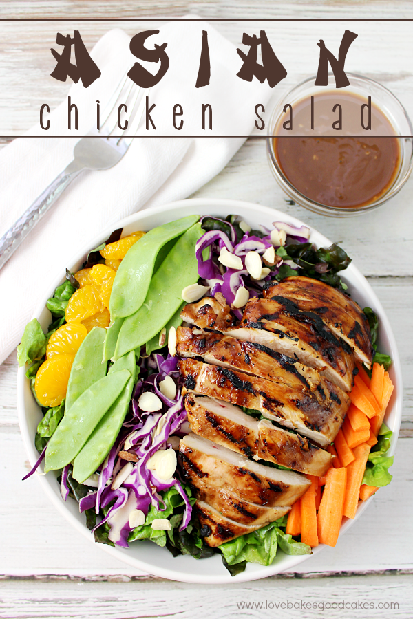 Asian Chicken Salad in a bowl with a fork and salad dressing.