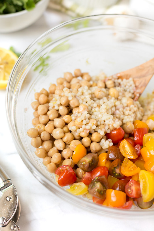 Adding the chickpeas and tomatoes to couscous salad