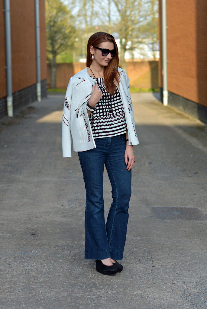 White cut out jacket, black and white boxy top, dark flared denim