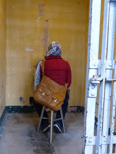 Woman sitting in cell listening to audio at the Ai Weiwei exhibit, Alcatraz