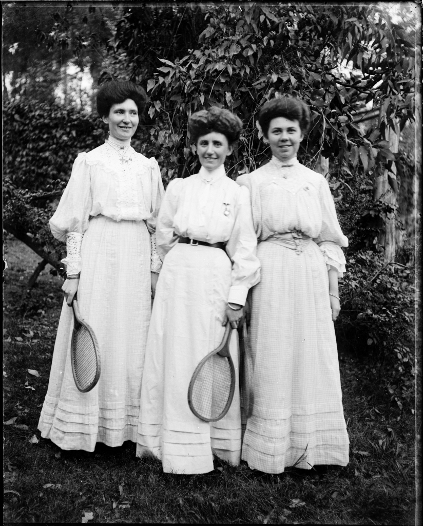 Three young women in light dresses holding tennis racquets, 1900