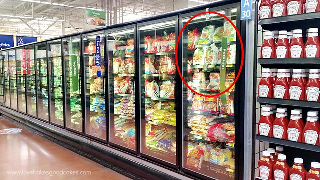 A grocery store isle of the frozen section with products on the shelf.