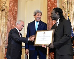 U.S. Secretary of State John Kerry looks on U.S. Senator Bob Corker shakes hands with Issa Kouyate of Senegal, a 2016 Trafficking in Persons (TIP) Report Hero, at the U.S. Department of State in Washington, D.C., on June 30, 2016. The TIP Report Heroes are nine men and women from around the world who fought against human trafficking. [State Department Photo/ Public Domain]
