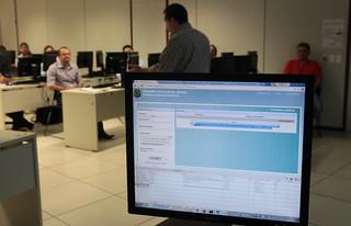 Em primeiro plano, monitor com sistema de Processo Judicial eletrônico; ao fundo, treinador do CNJ