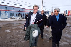 U.S. Secretary of State John Kerry and Senior Aide Jason Meininger laugh as bar patrons at the Navigator Inn invite the Secretary in for a drink as he walked through Iqaluit, Canada, just below the Arctic Circle, after the United States assumed a two-year chairmanship of the body during a meeting of its eight member nations and seven Permanent Representatives on April 24, 2015. [State Department photo/ Public Domain]