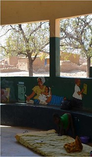 Using wall paintings to deliver the message-a brightly painted wall shows a mother feeding her baby with porridge while the older sister in the background holds a school book