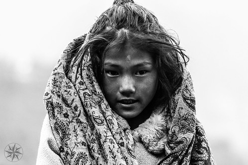 Nepali girl from Tibet living in Ghandruk, Népal. This young girl lives close to his mother's farm and works in the fields. This shoot was taken just after a storm and she was freezing but smile anyway. In Nepal people are so friendly.