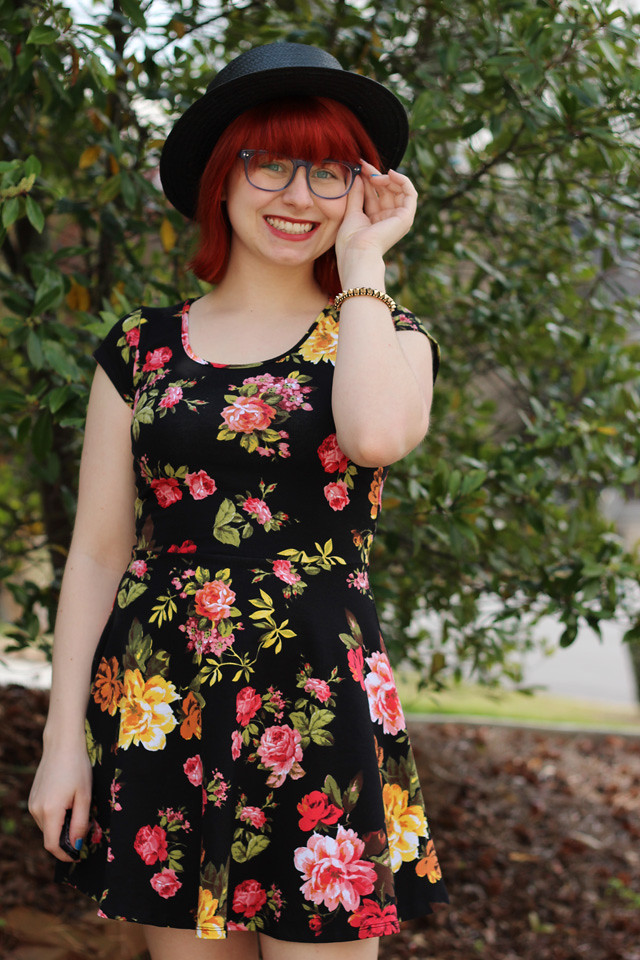 Dark Floral Print Skater Dress with Red Hair and Big Blue Glasses