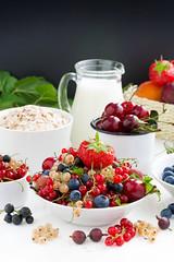fresh berries, fruit, cereal and milk. black backg…