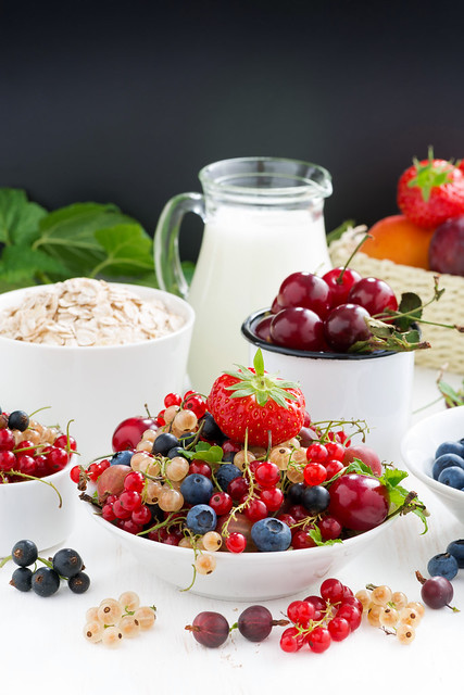 fresh berries, fruit, cereal and milk. black background for text