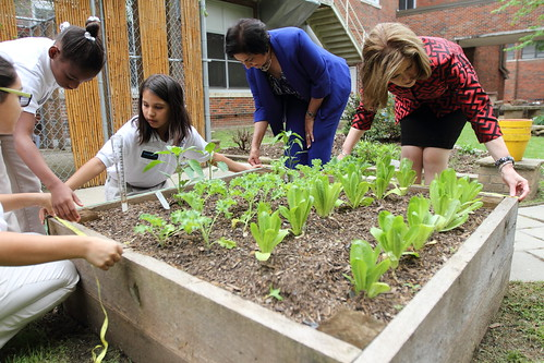 American Heart Association's Nancy Brown and Executive Director of the Dallas Independent School District's Food and Child Nutrition Services work with children at the Charles Rice Learning Center in their school garden