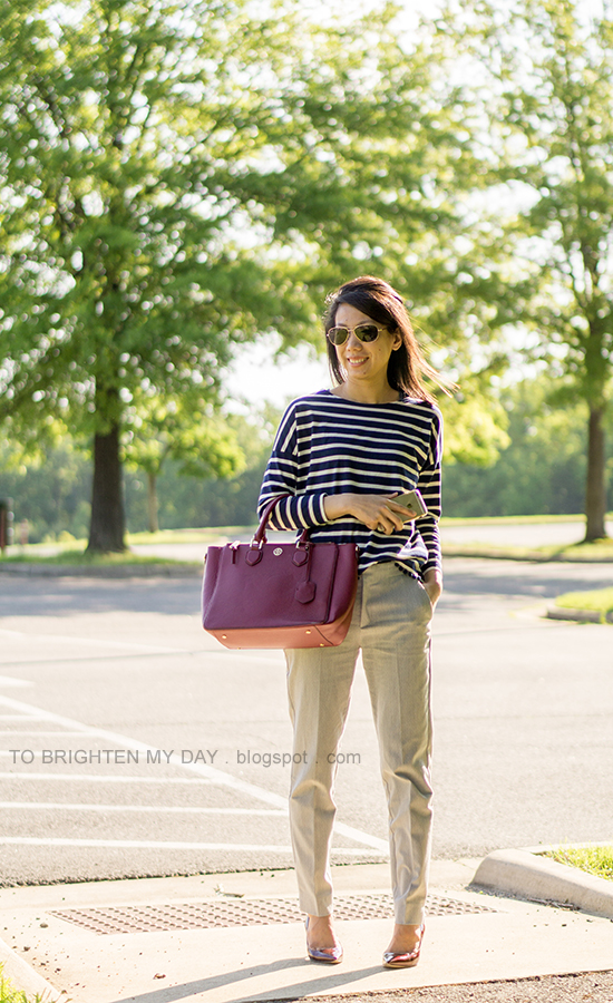 navy striped top with pom poms, gray pants, red purple tote, burgundy pumps