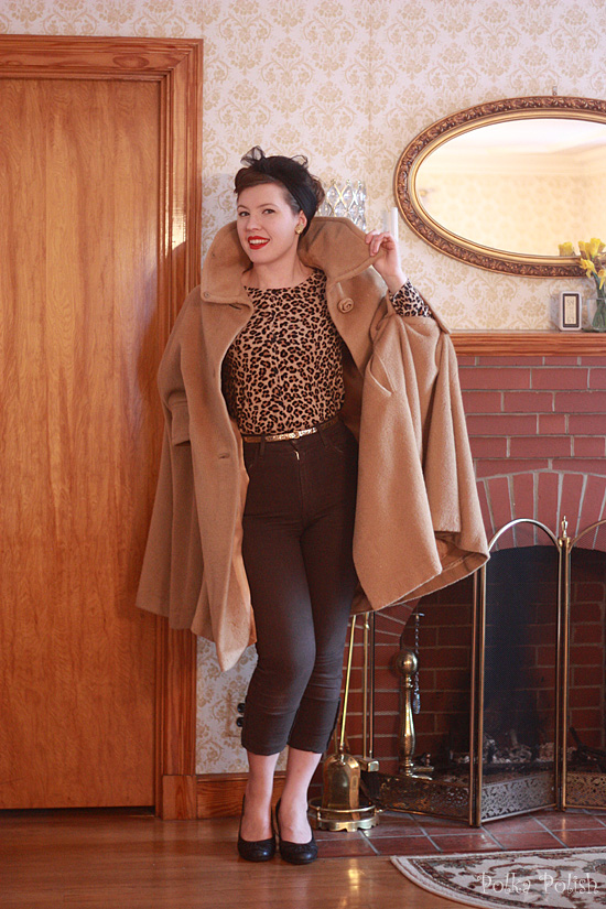 1960s-inspired outfit with a leopard print sweater, skinny jeans, and a vintage camel cape