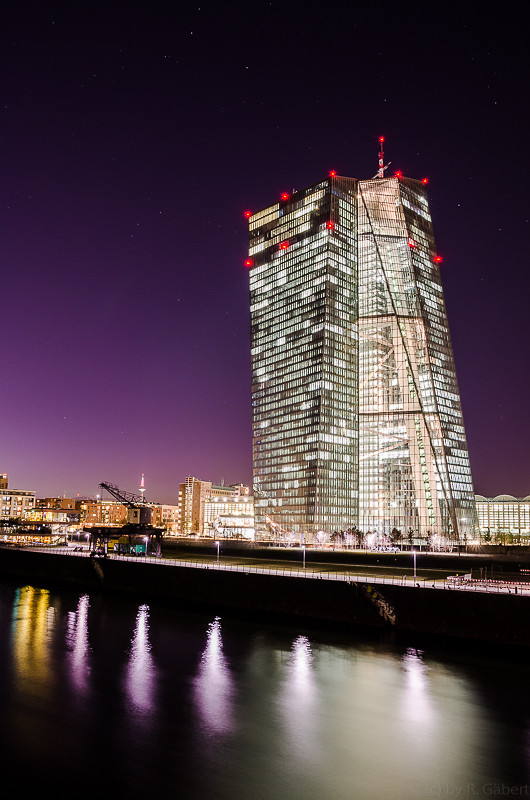 new european central bank building at night with a hand full of stars