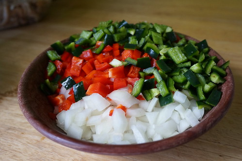 A wide shallow bowl filled with chopped onion, red bell pepper, and poblano pepper