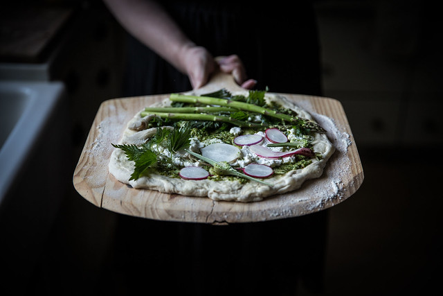 Homemade flatbread with fresh ricotta and asparagus along with a garlic pesto